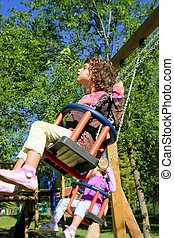 girl swinging on swing happy in trees outdoor