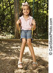 Girl swinging on swing.