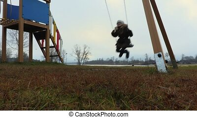 Girl swinging on the swing at outdoor