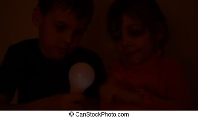 girl switchs on and off light bulb, which boy holds in hand