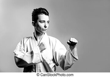 girl, Taekwondo is martial Stoke hands in fists, focused, serious look in the Studio on gray isolated background
