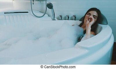 Girl take bath full of foam in bathroom. Smoking electronic cigarette. Steam