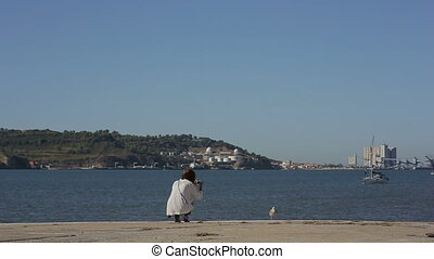 Girl takeing picture of yacht and albatros at the river in...