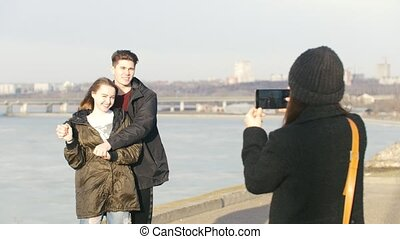 Girl takes a photo for happy couple on the waterfront in...