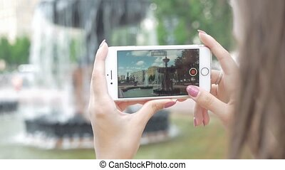 Girl takes a picture of a beautiful city fountain on the phone.