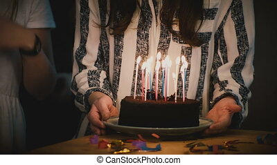 Girl takes and holds birthday cake with candles. Making a wish. Surprise party anticipation. Festive celebration mood 4K