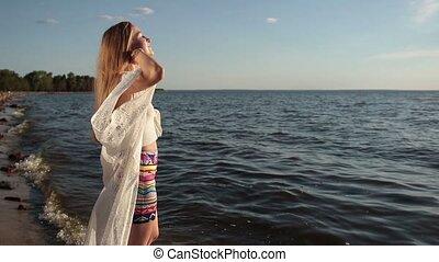 Girl takes deep breath enjoying fresh air on beach -...
