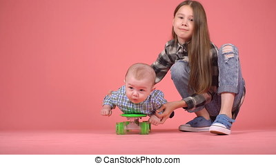Girl takes her brother on a skateboard