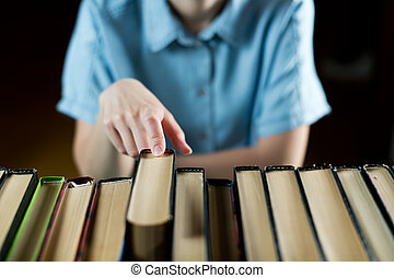 girl takes one book from a row of books, close-up of a hand, selective focus