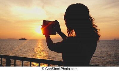 Girl takes photos of sunset on mobile phone camera on her vacation. slow motion.