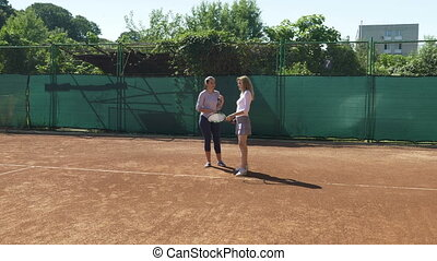 Girl takes tennis classes with her coach on the field