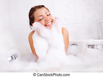 girl taking a bath - beautiful young brunette woman taking a...
