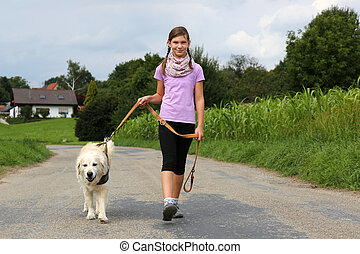 Girl taking a dog for a walk