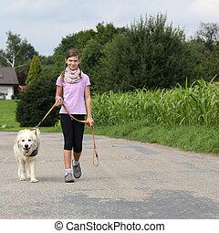 Girl taking a Golden Retriever dog for a walk