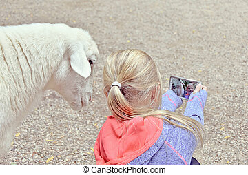 girl taking a selfie with goat