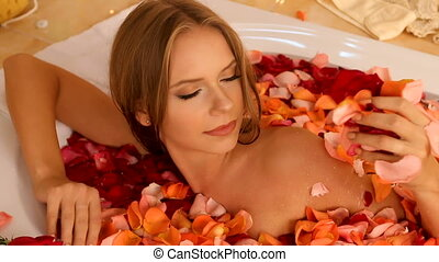 Girl taking bath with rose petals in bath. - Rose petals...