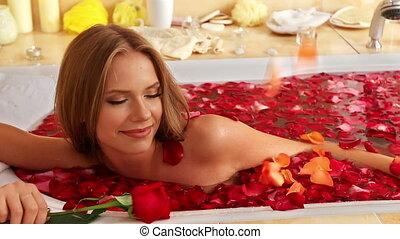 Girl taking bath with rose petals in bath. - Sensual tender...