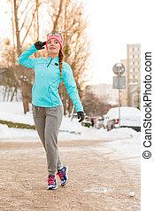 Girl taking morning walk in winter. Preparing for workout in...