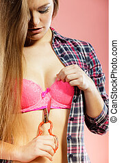Girl taking off bra, cutting her lingerie with scissors
