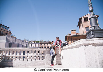 girl taking photo of boy sitting on balustrade in Rome