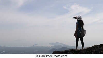 Girl Taking Photo Of Landscape From Mountain Top On Cell...