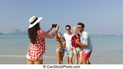 Girl Taking Photo Of People Group On Beach On Cell Smart...