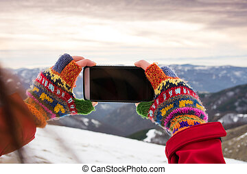 Girl taking picture of winter scenery with a smart phone