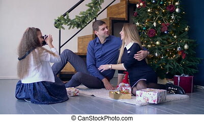 Girl taking pictures of her happy parents at Xmas - Little...