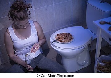 Girl taking pills - Young girl taking diet pills in bathroom