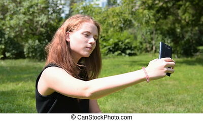 Girl taking selfie and using mobile phone in the park -...