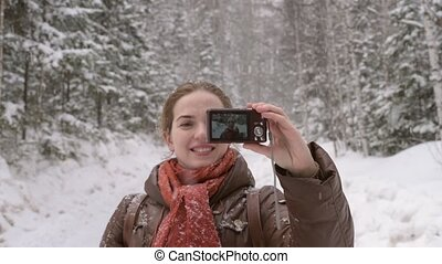 Girl taking selfie with a little camera