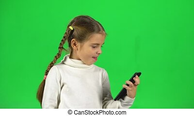 Girl talking at video chatting on phone in studio against green screen