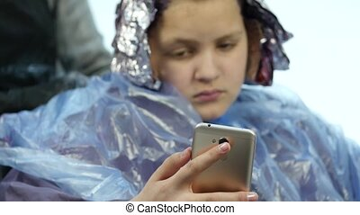 Girl talking on a phone while hairdresser makes hairstyle,...