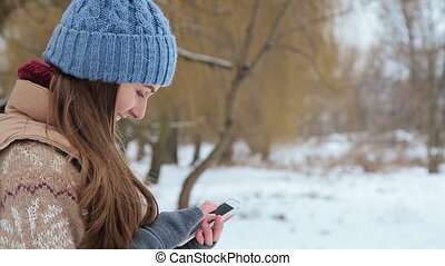 girl talking on a smartphone in the winter park