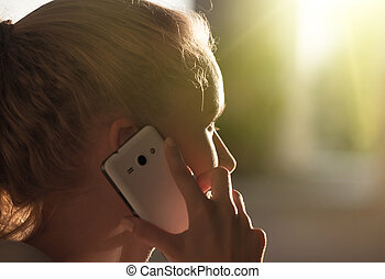 Girl talking on mobile phone in the evening