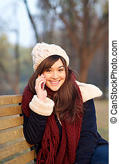 Girl talking on mobile phone on bench in park
