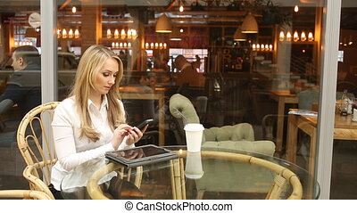 girl talking on the phone in a cafe. waving his hand in greeting. waiting for friends