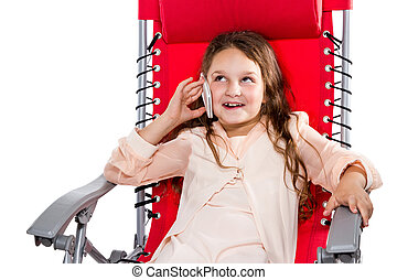 Girl talking on the phone sitting in an armchair