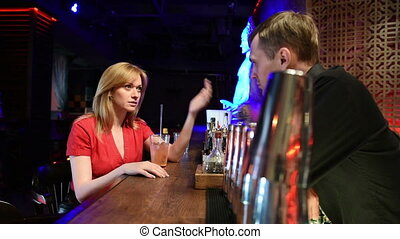 girl talking to the bartender. night life.