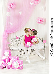 Girl talking whispering secret to friend in birthday party, present to sister pink gift boxes