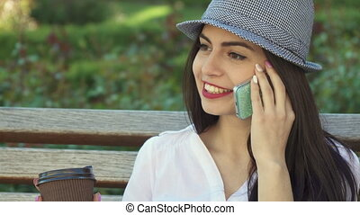 Girl talks on the phone on the bench
