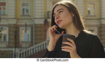 Girl talks on the phone on the street of the city