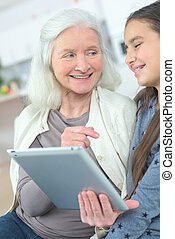 girl teaching grandmother how to use a tablet