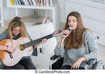 girl teaching her friend to play guitar