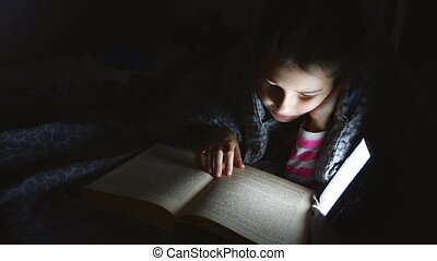 girl teen child reads book reading night with flashlight...