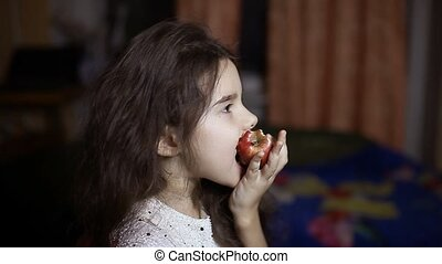 girl teen eating an apple sitting in room in evening fruit...