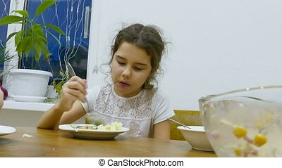 girl teen eats food hungry lettuce at table