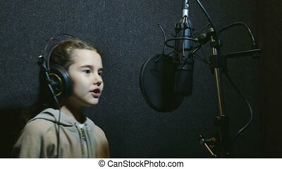 girl teen in headphones singing into microphone recording studio