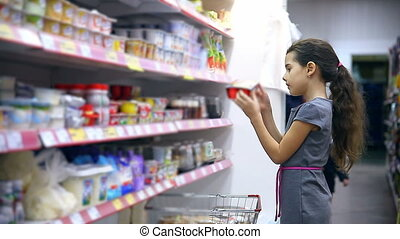 girl teen in supermarket to buy dairy yogurt food