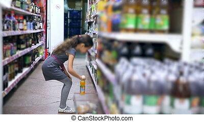 girl teen in supermarket to buy Juice water cola